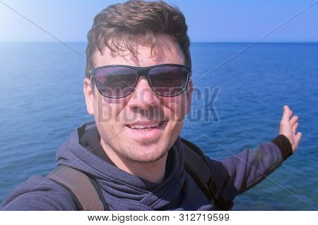 Happy Young Man Talks Video Chats Selfie Smartphone On Sea Beach Waves Hand Greets And Smiles At Cam