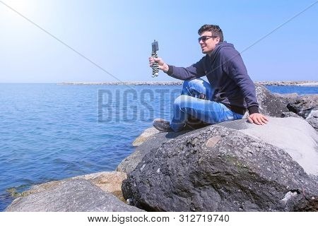 Man Talks Video Chat At Sea On Smartphone With Small Tripod Sits On Stone. Young Guy Traveller Share