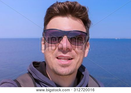 Portrait Of Young Guy On Sea Background. Man Blogger Traveller Selfie Camera Talks About Vacation At