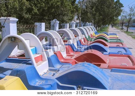 Colored Catamarans On The Waterfront Near The Sea Along The Fence. Catamaran Rental. Catamarans Trav