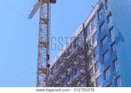 Multi-storey House Under Construction On The Background Of The Blue Sky Next To The Construction Cra