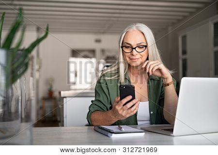 Happy senior woman using mobile phone while working at home with laptop. Smiling cool old woman wearing eyeglasses messaging with smartphone. Beautiful stylish elderly lady browsing site on cellphone.