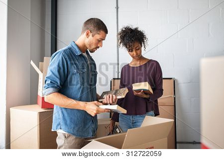 Multiethnic couple reading books while unpacking stuff after relocating to a new flat. Young man and african woman packing cardboard boxes with books. Guy and girl moving house.