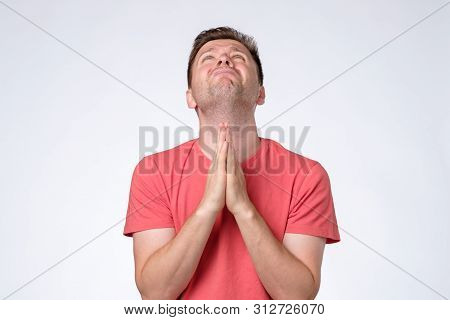 Worried Young Caucasian Man Put Hands Together Ask For Help Forgiveness In Prayer Gesture