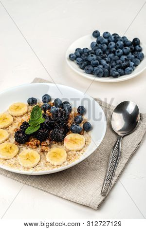 Oatmeal Porridge With Bananas, Walnuts, Blackberries, Blueberries, Honey And Mint In A White Bowl On