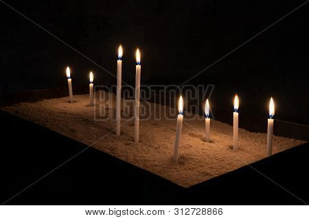 Several Burning Votive Candles In A Square Bowl Filled With Sand In A Very Dark Room
