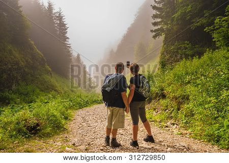 Couple Of Hikers On The Trail In The Mountains Admiring The Gorge On A Misty Morning
