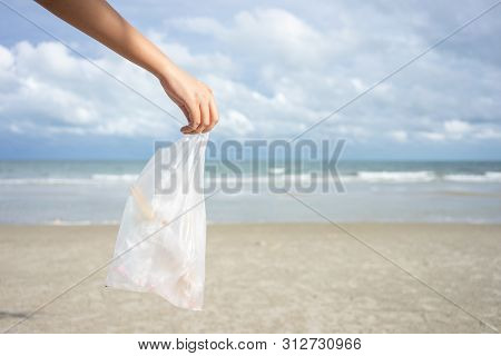 Woman Hand Picking Up Used Plastic Bag On Sand Beach, Cleaning Seaside Beach.  Environmental Polluti