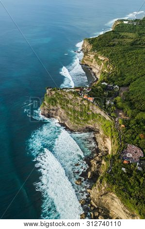 Aerial View Of Uluwatu Temple In Bali, Indonesia. Beautiful Balinese Landscape With Huge Waves And R