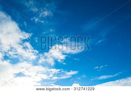 Blue dramatic sky background - colorful sky clouds lit by evening sunset light. Vast sky landscape scene, blue sky background