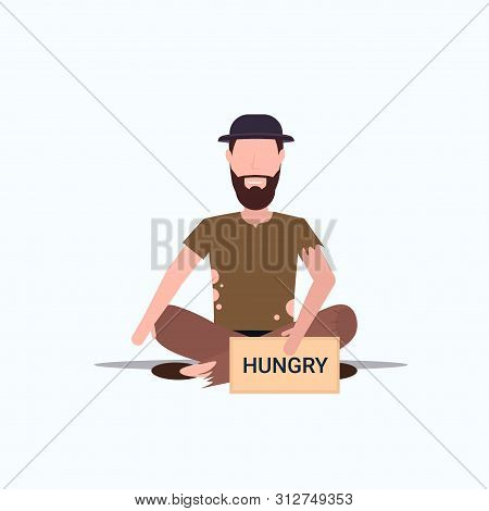 Bearded Man Beggar In Hat Holding Sign Board With Hungry Text Tramp Sitting On Floor Begging For Hel