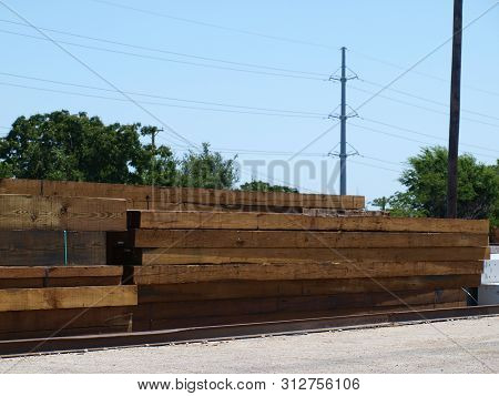 Cut Timbers For Railroad Ties And Trestle Work Stacked In An Off Load At A Rail Yard.