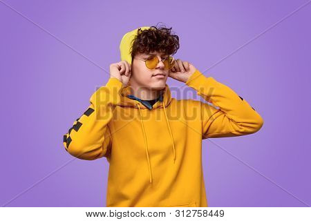 Trendy Youngster In Yellow Outfit Pulling Hat On Curly Hair And Closing Eyes Against Vivid Violet Ba