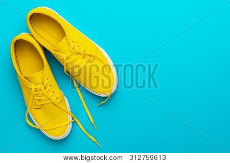 Top View Photo Of Pair Of Untied Sneakers. Minamalist Flat Lay Image Of Yellow Summer Sneakers. Yell