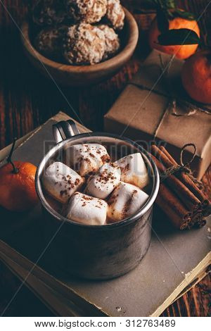 Rustic Metal Mug Of Hot Chocolate With Marshmallows. Tangerines, Cinnamon Sticks Bunch And Gingerbre