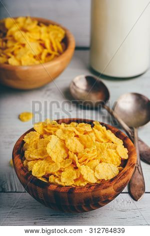 Rustic Bowl Of Corn Flakes With Spoons And Bottle Of Milk