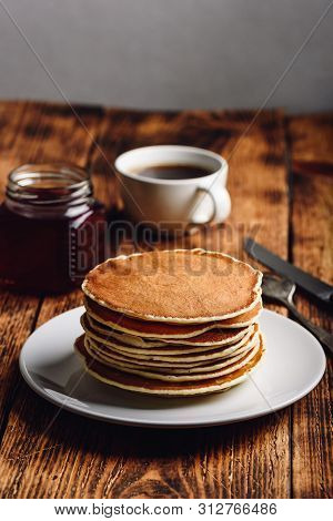 Stack Of Pancakes On White Plate Over Wooden Surface