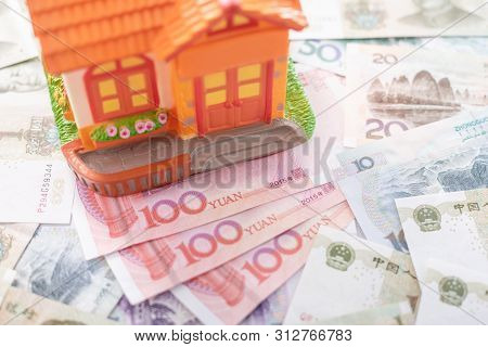 Buy Or Rental The House Concept. Close Up Several Banknote Currency Chinese Yuan (cny Or Rmb) And Ho