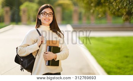 Asian Student With Backpack Carrying Books After Study, Walking In Campus