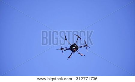 Close-up Of Quadcopter Flying In Sky. Clip. Large Quadcopter With Powerful Motors Flying On Backgrou