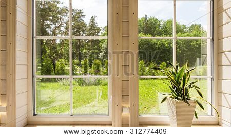 Bright Interior Of The Room In Wooden House With A Large Window Overlooking The Summer Courtyard.