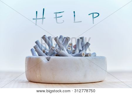 Marble Ashtray Full Of Cigarettes And The Word Help Written Above. Concept For Cigarettes Addiction,