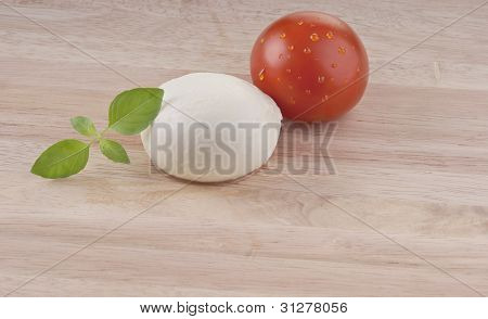 fresh mozzarella on chopping board with tomato and basil