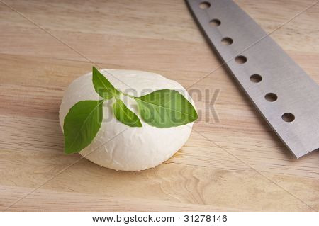 fresh mozzarella on wooden chopping board with knife