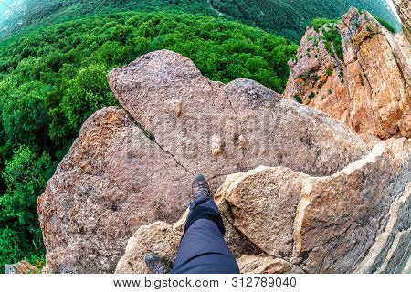 Man Hiker Steps On The Edge Of Mountain Rock Above Precipice With Green Forest Trees Underneath. Cau