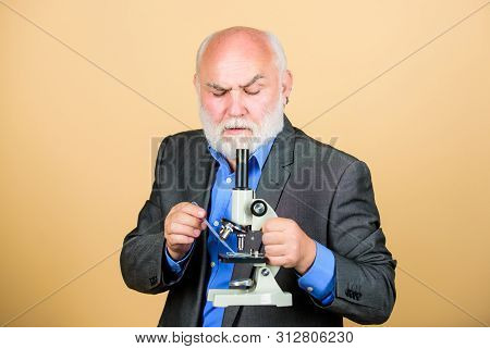 Mature Man Formal Suit With Microscope. Doctoral Work And Postdoctoral Employment. Molecular Biology