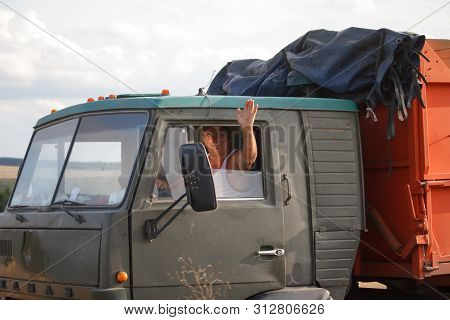 Cheerful Male Driver Kamaz Waving His Hand Out Of The Car During The Harvest