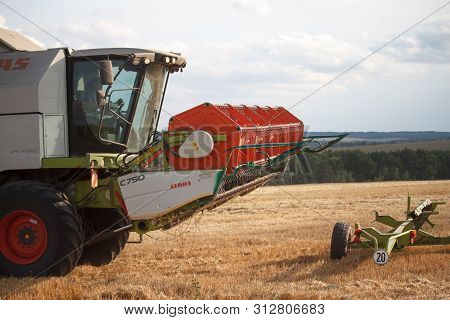 Combine Harvester With A Raised Mechanism Rides The Stubble After Harvesting Wheat Fields For Harves