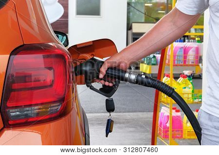 Pumping Gasoline Fuel In Orange Car At A Gas Station. To Fill Car With Fuel In Petrol Station. Petro