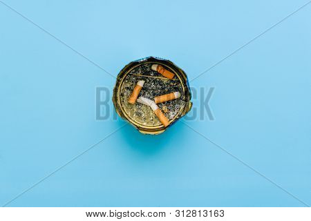 Ashtray With Cigarette Butts And Ash On A Blue Background. Unfinished Cigarettes In An Iron Can. Sto