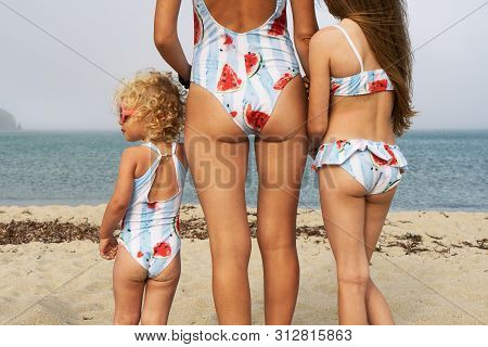 Mom And Two Daughters In The Same Swimsuit On A Sandy Sea Beach. The Younger Daughter With Curly Hai