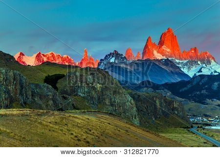 The grand crimson dawn over the mountain range Fitzroy. Mountain peak in Patagonia in the border area between Argentina and Chile. Magnificent and picturesque mountain range, illuminated by  sunrise
