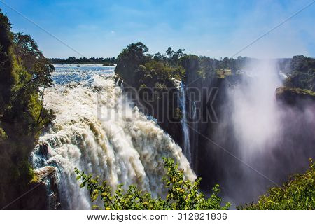 Colossal Victoria Falls. The waterfall is located on the Zambezi River, in Victoria Park, on the border between Zambia and Zimbabwe. Journey after the wet season.  Concept of extreme and photo tourism