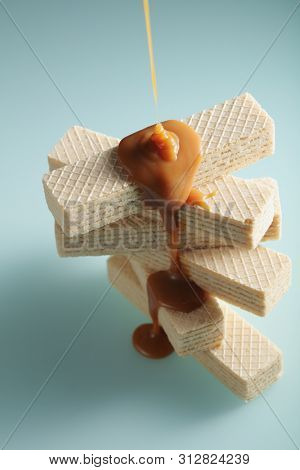 Caramel sauce flows down a stack of wafers against cyan background