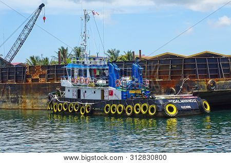 Labuan,malaysia-sept 23,2018:a Tugboat Maneuvers Vessel By Pushing Or Towing To The Port Of Labuan I