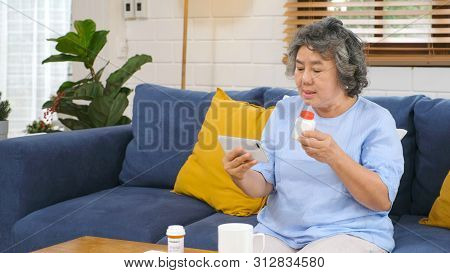 Senior Asian Woman Holding Bottle Of Pill Make Video Conference Phone Call To Doctor Consulting Abou