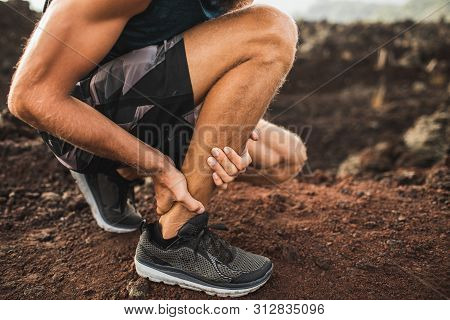 Achilles Injury On Running Outdoors. Man Holding Achilles Tendon By Hands Close-up And Suffering Wit