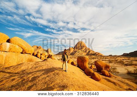Young girl in Spitzkoppe area with picturesque stone arches and unique rock formations in Damaraland Namibia