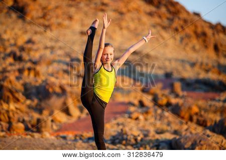 Casual portrait of little girl outdoors on summer day practicing gymnastics