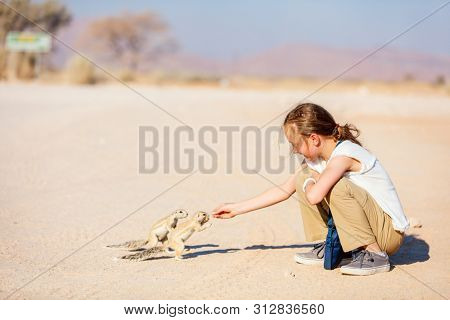 Adorable young girl feeding little ground squirrels outdoors