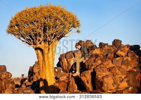 Teenage boy at quiver tree forest near Keetmanshoop in Namibia at sunset