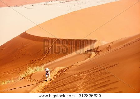 High angle view of young woman climbing up famous red sand dune Big Daddy in Sossusvlei Namibia