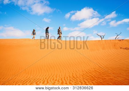 Family of father and two kids climbing up red sand dune in Namib desert