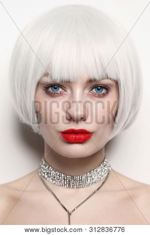 Vintage style portrait of young beautiful woman with platinum blonde hair and red lips