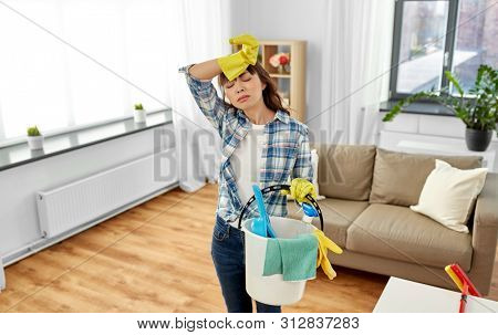 people, housework and housekeeping concept - tired asian woman or housewife holding bucket full of cleaning stuff at home