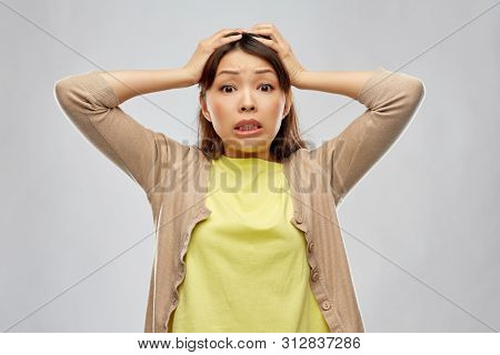 people, emotion and expression concept - terrified asian woman holding to her head over grey background